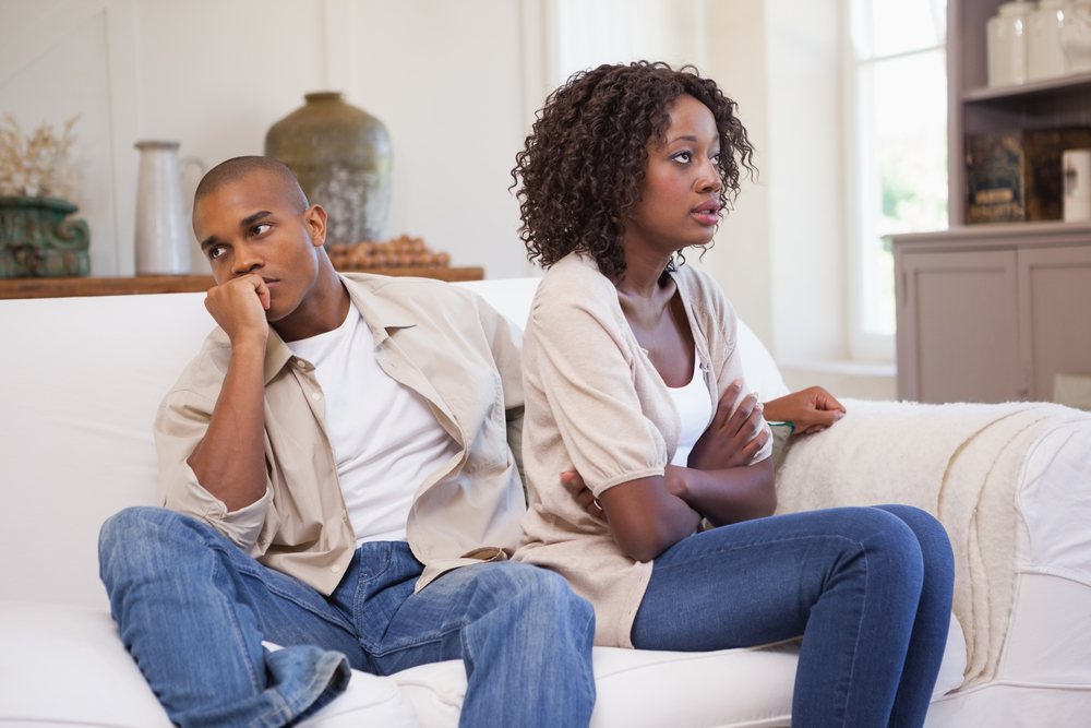 Young Black couple arguing, facing away from one another